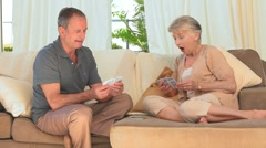 Elderly couple playing cards Stock Footage