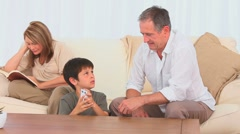 Little boy dealing cards to his grandfather Stock Footage