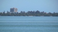 Stock Video Footage of Water scenic yacht idles by with condo in bg h264