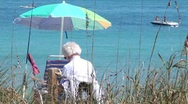 Beach scenic older woman reads while people in a boat fish h264  Stock Footage