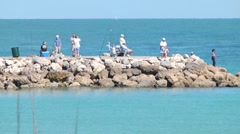 Beach scenic people fishing on rock jetty h264 Stock Footage