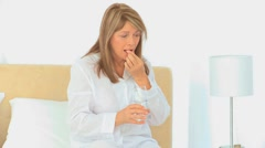 A sick mature woman taking pills - stock footage