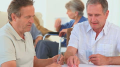 A game of cards between two elderly friends Stock Footage