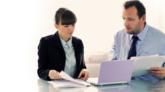 Young business couple working with documents in front of the laptop - stock footage