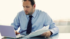Happy businessman working with documents and laptop  - stock footage