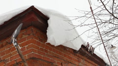 Cleaning snow from roof eaves cornice - countryside house Stock Footage