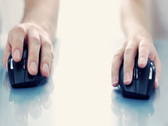 Female and male hand using a wireless computer mouse on reflective table Stock Footage