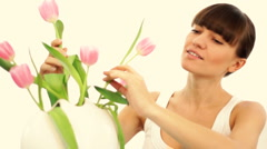 Beautiful woman putting tulips into vase Stock Footage