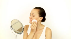 Young attractive woman cleaning her face with cotton pad Stock Footage