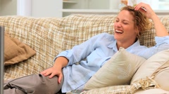 Curly-haired woman laughing in front of her tv - stock footage
