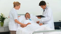 Doctors examining a sick man Stock Footage