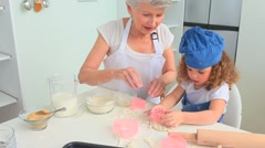 Grandmother baking with her grand daughter Stock Footage
