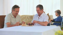 Men playing chess while their wives are speaking Stock Footage