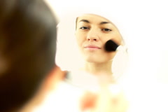 Beautiful young woman applying natural beauty make-up in the mirror, isolated Stock Footage