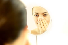 Beautiful young woman applying natural beauty make-up in the mirror Stock Footage