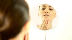 Attractive young woman searching for pimples in the mirror Stock Footage