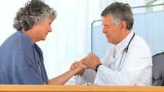 Mature doctor taking the pulse of his patient Stock Footage