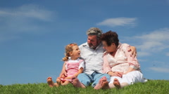 Mature couple and granddaughter sit something sing on grass - stock footage