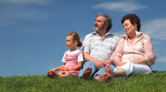 Mature couple and granddaughter sat on grass with bare feet talking Stock Footage