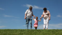 Couple stand on grass, granddaughter jumps and squats holding hands Stock Footage
