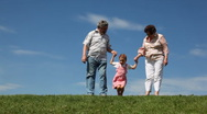 Stock Video Footage of Couple stand on grass, granddaughter jumps and squats holding hands