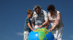Couple with grandson stand and study Earth by inflatable ball Stock Footage