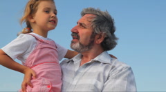 Senior with granddaughter on hands,he something shows and tells her Stock Footage