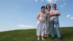 Couple stands embracing with adult daughter on grass - stock footage