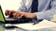 Businessman working on laptop and looking through documents Stock Footage