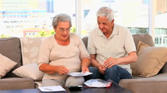 Mature couple calculating their domestics bills Stock Footage