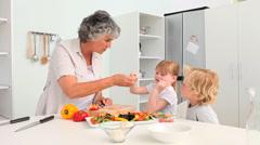 Grandmother cooking with her grandchildren Stock Footage