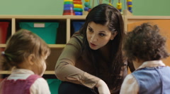 Teacher reading book to children in kindergarten Stock Footage