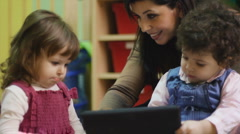 Teacher using tablet pc with children at school - stock footage