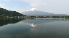000006 Snow Topped Mount Fuji Reflected Rippling Lake - stock footage