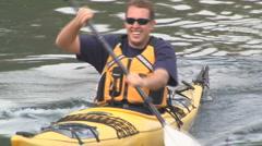 Young man paddles kayak Stock Footage
