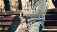 Young lonely sad boy with skateboard sitting on park bench, steadicam shot Stock Footage