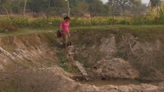 Cambodia: Woman fills Watering Cans Stock Footage