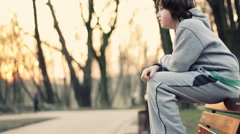 Young lonely sad boy sitting on park bench, steadicam shot - stock footage