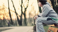 Young lonely sad boy sitting on park bench, steadicam shot Stock Footage