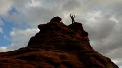 Man Waves Atop Red Rocks Stock Footage