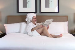Woman reads paper in bed V2 - NTSC Stock Footage