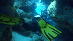 Scuba divers swimming through cave Stock Footage