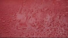 Rain drops falling on red surface 2 big streams Stock Footage