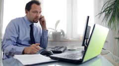 Angry businessman in the office talking on mobile phone Stock Footage