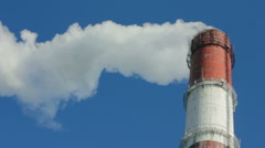 factory chimney with smoke under blue sky - stock footage
