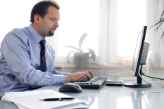 Unhappy businessman working on computer and looking to the camera - stock footage