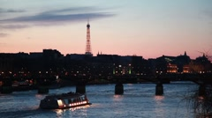 Ship moves on river to iron bridge of night in Paris Stock Footage