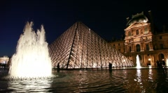 Tourists walk near fountains in front of Louvre Stock Footage