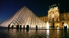 Tourists walk near piramid in front of Louvre Stock Footage