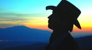 Stock Video Footage of Cowboy Plays Guitar on Mountain at Sunset 09
